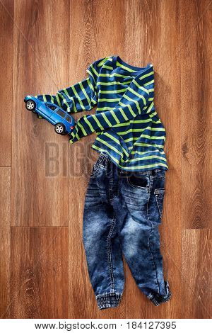 Spring or summer children's clothes and blue toy car on the wooden background. Colorful jacket in the stripes and blue jeans. Casual children's style. Clothes for little boys. Concept of the children's fashion.