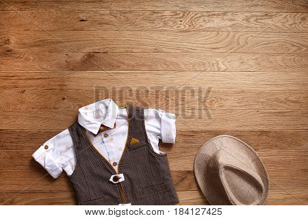 Top view photo of the boy's clothes on the wooden background. White shirt with print, brown vest, bowtie and hat. Cute clothes for little boys. Concept of the children's fashion. Spring or summer children's clothes.