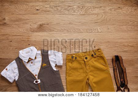 Top view photo of the boy's clothes with accessories on the wooden background. White shirt with print, brown vest, bowtie, brown pants and suspenders. Cute clothes for little boys. Concept of the children's fashion.