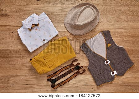 Top view photo of the boy's clothes with accessories on the wooden background. White shirt with print, brown vest, bowtie, brown pants, suspenders and hat. Cute clothes for little boys. Concept of the children's fashion.