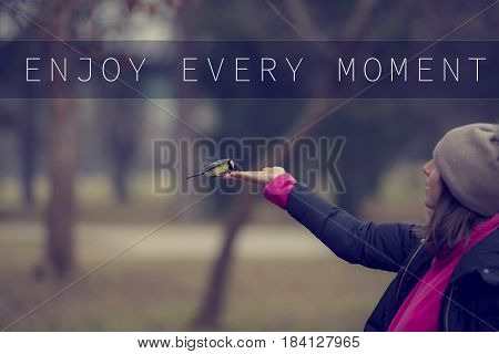 Enjoy every moment text over woman stretching arm feeding great tit bird standing outdoors.