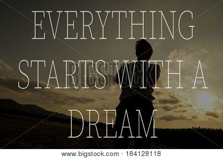 Everything starts with a dream text over silhouette of a businessman at sunset standing with folded arms.