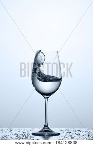 Splashing cleaner water wave in the wineglass while standing on the glass with drapes against light background. Pure, transparent, useful water. Care for the environment. Concept of the healthy lifestyle.