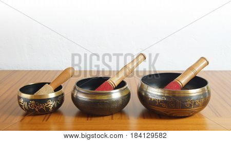 Three Tibetan bowls on a wooden table with white wall background