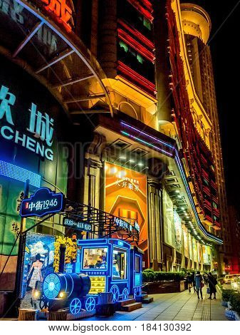Shanghai, China - Nov 3, 2016: Night scene on Nanjing Road Pedestrian Street - outdoor store in style of locomotive decorated with neon lights selling ice cream and other dairy products.