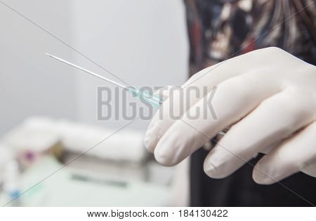 Professional holding the needle cannula on hand for piercing. Closeup