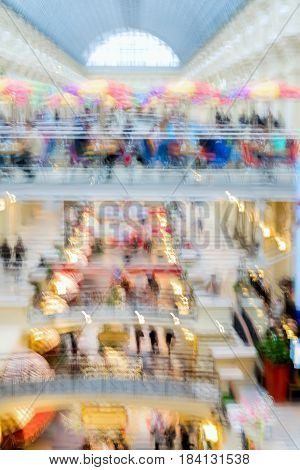 Abstract defocused motion blurred young people walking in the shopping center. Shopping arcade, a top view of two floors, Cafe with parasols For background, urban lifestyle concept,