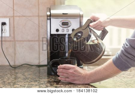 Male hand pour dark coffee from pot into cup on kitchen counter with morning light coming in from window in background. Select focus on hand with light effect applied.