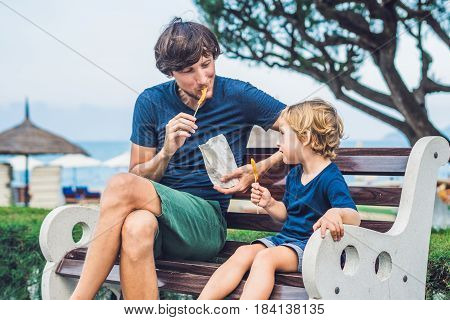 Father And Son Eat Fried Sweet Potatoes In The Park. Junk Food Concept