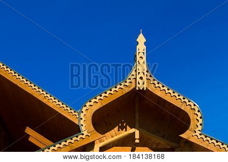 Traditional russian wooden architecture carved fronton and cottage roof.