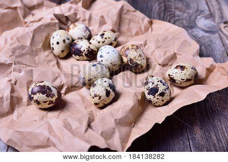 Fresh quail eggs on brown paper close up