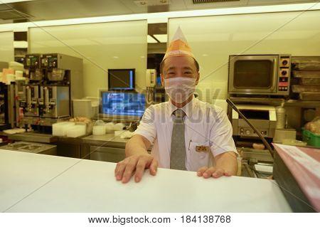 HONG KONG - OCTOBER 25, 2015: indoor portrait of a worker at Cafe de Coral restaurant. Cafe de Coral is a fast food franchise based in Hong Kong.