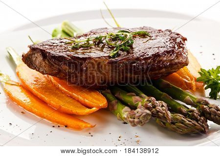Grilled beefsteak with asparagus and carrot on white background
