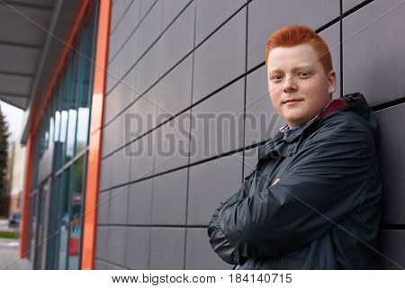 A Horizontal Portrait Of Redhead Guy With Freckles Wearing Black Jacket Posing Over Black Wall Of Th