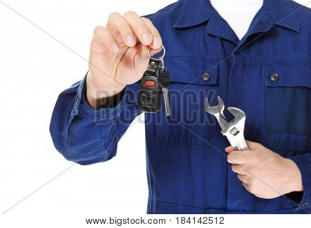 Auto mechanic with car key and tools on white background, closeup