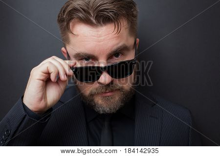 A Brutal Man With A Beard And A Stylish Hairstyle In A Black Suit Looks Appallingly At The Camera, D