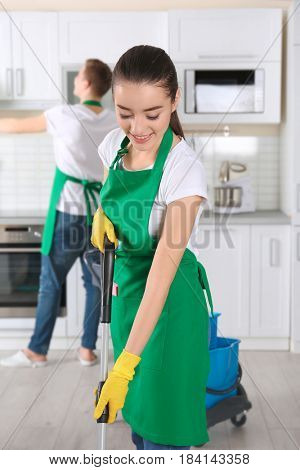 Young female cleaner at work in kitchen