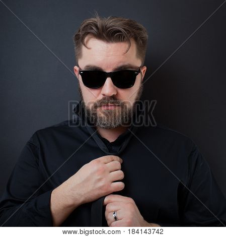 A Brutal Man With A Beard And A Stylish Hairstyle In A Black Shirt Adjusts His Tie. The Businessman
