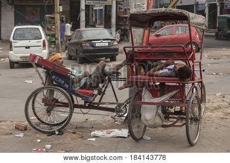DELHI INDIA-JUN 11 : driver sleep in his rickshaw bike at ajmeri gate in old delhi area of delhi on june 11 2015 india. some rickshaw driver is homeless he use bike as house