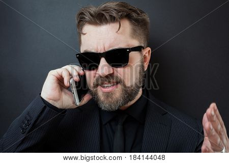 A Businessman In A Black Suit Swears By Phone With His Subordinates. A Man In Sunglasses Speaks On T