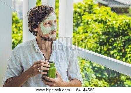Spa Man Applying Facial Green Clay Mask. Beauty Treatments. Fresh Green Smoothie With Banana And Spi