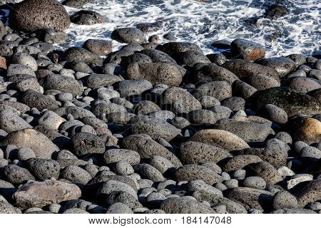 Rounded Volcanic Black Stones On The Beach