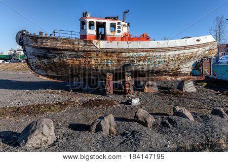 Old wooden boat on shore in the Reykjavik's harbor in Iceland.