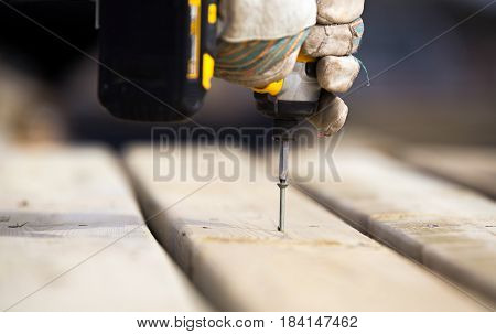 Close up of hands wearing work gloves gripping a power drill putting a screw into a piece of wood