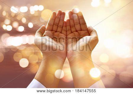 Muslim man praying to god with bokeh background