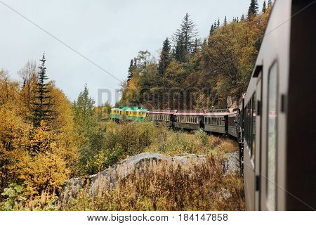 White Pass and Yukon route railroad train ride on old transport rails in Alaska, USA. Nature landscape of Alaska travel cruise excursion.