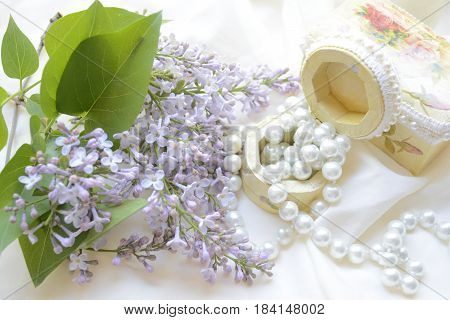 branch of lilac, beads and boxes on a light drape