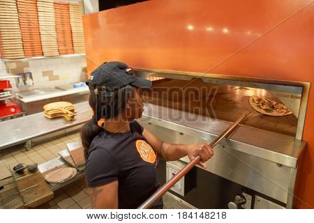 CHICAGO, IL - CIRCA MARCH, 2016: worker cook pizza at Blaze Pizza restaurant. Blaze Pizza LLC is a Pasadena, California-based chain within the fast-casual dining restaurants category.
