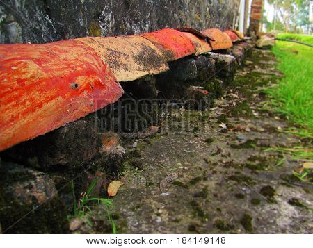 Composition of bricks, roof tiles, stone-ground, and grass at a farm in Latinamerica