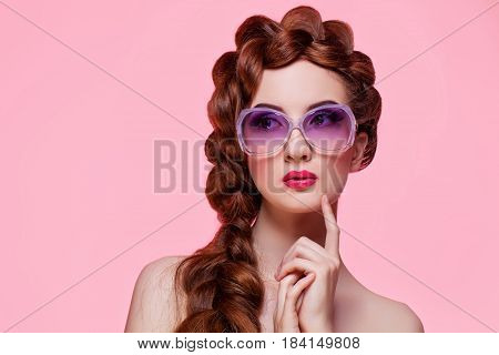 Beautiful young woman with red braided hair, bright make-up and purple sunglasses over pink background. Pin up style. Copy space.
