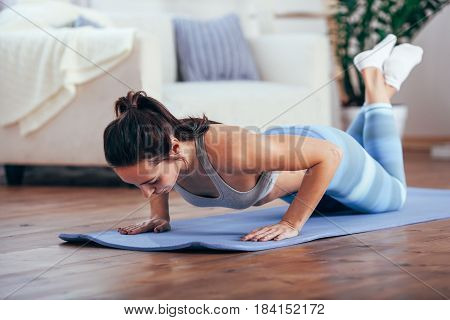 caucasian women exercise indoor at home she is acted push-ups