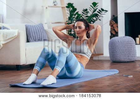 mid adult brunette woman wearing blue sportswear training abdominals at home