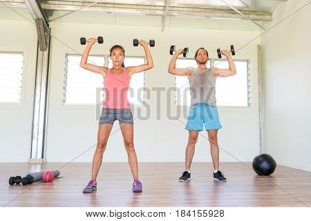 Fitness couple working out together training arms doing overhead shoulder press with dumbbells weights or standing dumbbell press exercise at gym. Asian woman and Caucasian man.