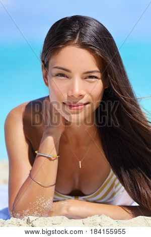 Asian beauty bikini woman beach vacation portrait of multiracial woman relaxing on beach. Young chinese model with perfect skin wearing bikini and jewellery - bracelet and necklace.
