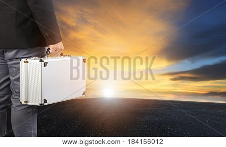 business man and steel breifcase standing on wide road and sun rising sky for business opportunity concept