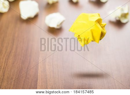 Yellow Crumpled Paper Ball Floating Around White Paper Ball On Wood Table, Business Concept