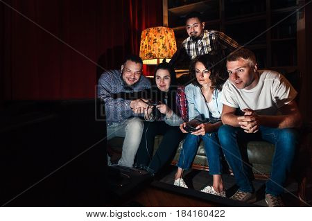 Company of five friends play video game at home, fun entertainment, exciting, competition. Concentration, tension, positive emotions, leisure concept