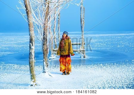 Woman on ice lake in beautiful ethno dress and beautiful frozen trees