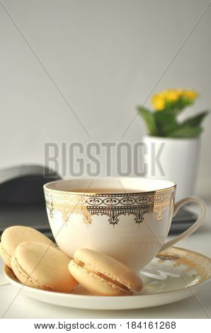 Cup of tea and vanilla French macaroons with yellow plant copy space
