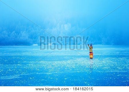 Woman on ice lake in beautiful ethno dress. Prayer for the lake