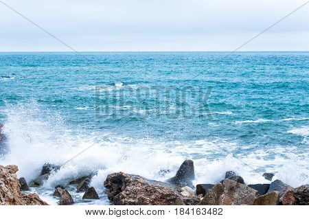 Nature background with waves break against the sea stony shore