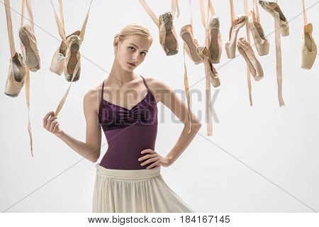 Beautiful ballerina in a violet top and a cream skirt stands on the light background in the studio. Around her there are many hanging beige pointe shoes. She holds a ribbon of the ballet shoe.