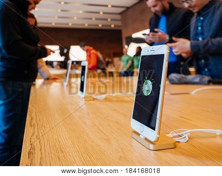 STRASBOURG FRANCE - APR 27 2016: Latest iPhone 7 and iPhone 7 Plus in Apple Store with screensaver dedicated to Earth Day - customers shopping testing in the background