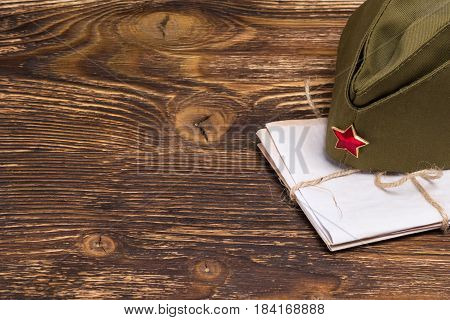 stack of old letters under the military cap on the table place the graphic to the left