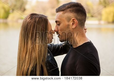Portrait of young in love couple embracing each other in the park. In love and relationship. Happines and love