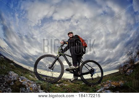 Portrait of the young cyclist standing with bike on the rocks against dramatic sky with clouds. Sportsman in the black sportwear, helmet, sunglasses and with red backpack. Fisheye. Beautiful landscape. Spring season in the countryside.